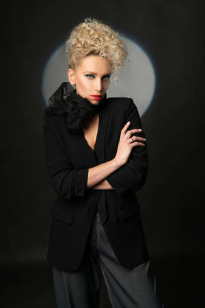 A beautiful blonde girl with an elegant hairstyle and large breasts, wearing a bra, trousers, scarf and a blazer, fashionable poses in the dark. Trendy, commercial and advertising design 免版税图像