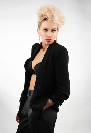 A beautiful blonde girl with an elegant hairstyle and large breasts, wearing a bra, trousers and a blazer, poses isolated on white. Trendy, commercial and advertising design