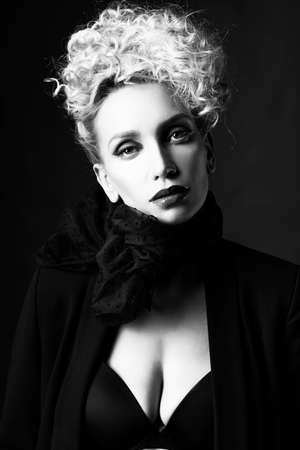 A beautiful blonde girl with an elegant hairstyle and large breasts, wearing a bra, scarf and a blazer, poses in the dark. Trendy,monochrome, black and white, noir design. Close Up portrait