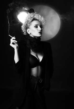A beautiful blonde girl with an elegant hairstyle and large breasts, wearing a bra, trousers, scarf and a blazer, smokes a cigarette near the spotlight. Trendy, monochrome