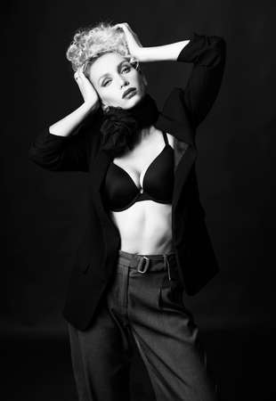 A beautiful blonde girl with an elegant hairstyle and large breasts, wearing a bra, trousers, scarf and a blazer, fashionable poses in the dark. Monochrome, black and white, noir design