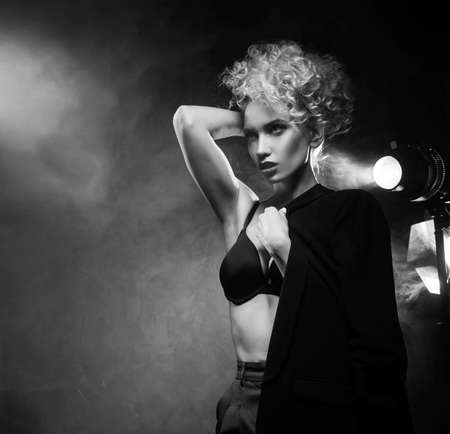 A beautiful blonde girl with an elegant hairstyle and large breasts, wearing a bra, trousers and a blazer, artistically poses in the rays of spotlights in the smoke. Cinematic, art, monochrome design Zdjęcie Seryjne