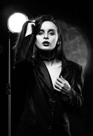 Beautiful slim girl model with red lips, wearing a black blazer, touches her hair with her hand on a dark background, posing next to a light lamp. Advertising, monochrome, black and white design