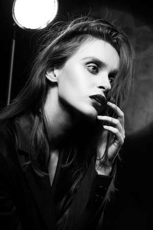 Beautiful braless slim girl, wearing a unbuttoned black blazer, with a slight frenzy and detachment in her eyes touches her face with her hand on a dark background, next to the light lamp. Monochrome