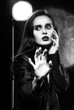 Beautiful slim girl model with red lips, wearing a black blazer, fearfully protects herself with her hand on a dark background, next to the light lamp. Advertising, trendy, monochrome design