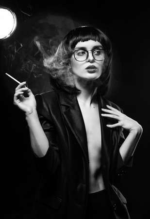 Beautiful braless slim girl with red lips, wearing a unbuttoned black blazer, glasses and brunette wig sensually smokes un a dark background next to the light lamp. Artistic monochrome noir design Stockfoto