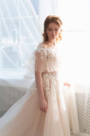 Beautiful natural redhead girl bride, with makeup, wearing a white dress, stands at the window next to a transparent curtain