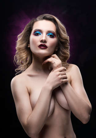 Beautiful topless busty girl with blue makeup poses on black and pink background, covering her breast with her hands. Fashionable, advertising and commercial portrait design Фото со стока