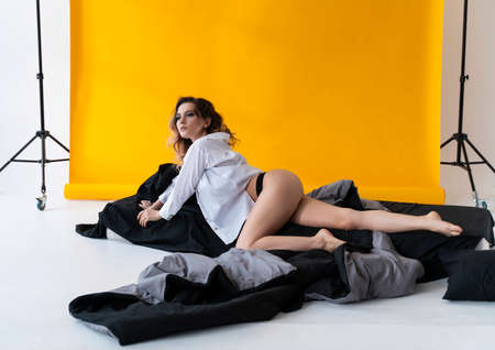 Beautiful busty girl wearing trendy lingerie and unbuttoned shirt, sensually relaxes in the bed near the yellow background. Fashionable, advertising, lifestyle and commercial design Фото со стока