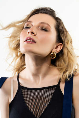 A beautiful girl wearing a black and blue casual trendy dress sensually poses in the wind at the white background. Fashionable, advertising, lifestyle and commercial design