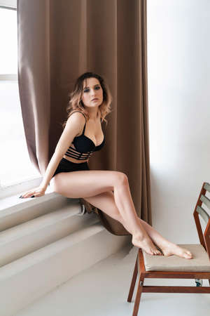 Beautiful busty girl wearing trendy lingerie is sitting on the windowsill. Fashionable, advertising, lifestyle and commercial design Фото со стока