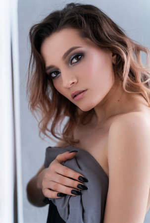 Beautiful busty topless girl wearing panties sensually covers her breast with the blanket at the white wall. Fashionable, advertising, lifestyle and commercial design