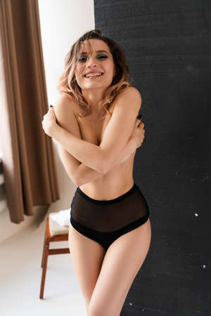 Beautiful busty topless smiling girl wearing trendy pantiescovers her chest hugging herself with her hands. Fashionable, advertising, lifestyle and commercial design