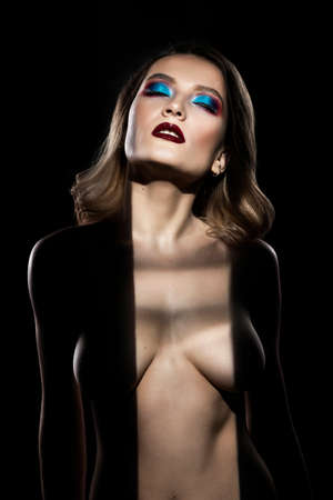 Beautiful topless busty girl with blue makeup. Her breast is hide in the deep dark shadows and seen only silhouette of her body. Conceptual, advertising, artistic design