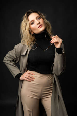 Beautiful girl wearing a casual trendy trousers, turtleneck glasses and raincoat posing on a dark background. Fashionable, advertising, lifestyle and commercial design