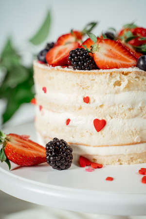 White berry cream cake decorated with strawberries and blackberries, among lilac flowers and green leaves. Food photography. Advertising and commercial close up design