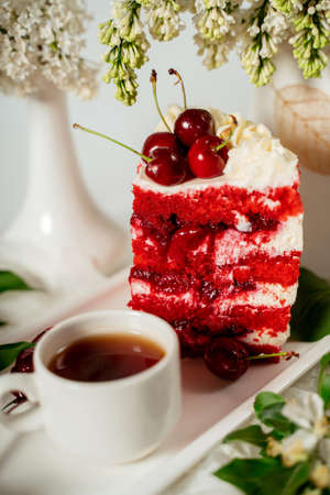 Slised red berry cake decorated with cherry berries and white cream, among lilac flowers and green leaves. Food photography. Advertising and commercial design