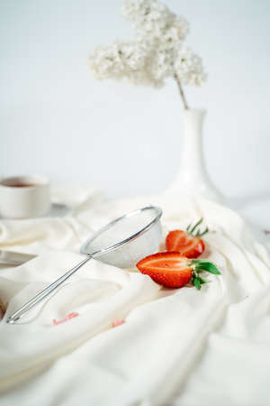 Sliced strawberry, lying next to a sieve for powdered sugar, on a white cloth, near the flowers of lilac. Food photography. Advertising and commercial close up design Фото со стока