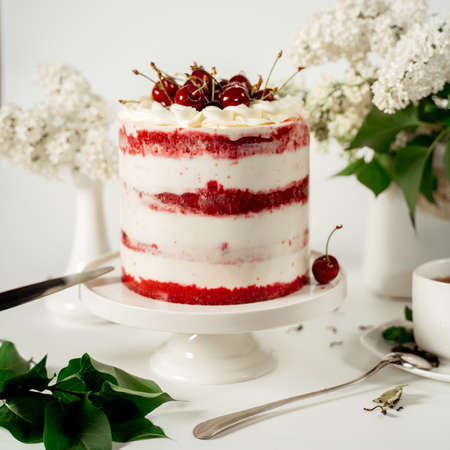 Red berry cake decorated with cherry berries and white cream, among lilac flowers and green leaves. Food photography. Advertising and commercial design