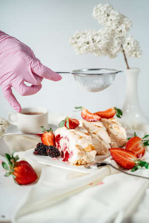 A gloved hand sprinkles sugar through a sieve with a meringue cake, garnished with nut chips and strawberries, among lilac flowers. Food photography. Advertising and commercial close up design