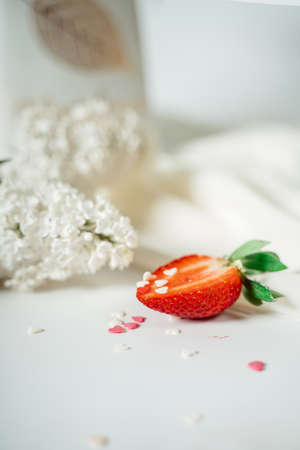 Sliced strawberry, on a white cloth, near the flowers of lilac. Food photography. Advertising and commercial close up design