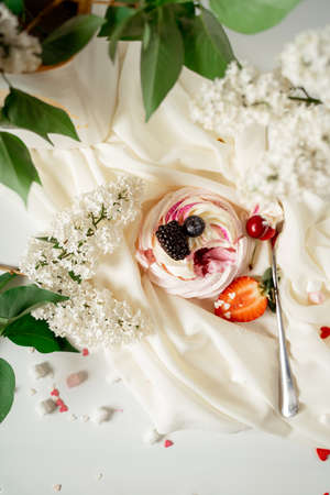 Meringue fruit cake garnished with cream and berries of cherries, blackberries and strawberries, among lilac flowers and green leaves. Food photography. Advertising and commercial close up design