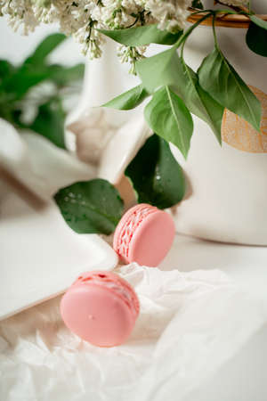Pink macaroon cookies among white flowers of lilac and green leaves. Food photography. Advertising and commercial close up design