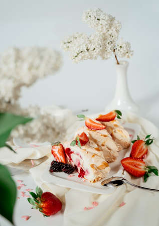 Fruit jam meringue cake garnished with hazelnut chips and strawberries, among lilac flowers. Food photography. Advertising and commercial close up design Фото со стока