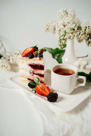 Sliced white berry cream cake decorated with strawberries and blackberries, among lilac flowers and green leaves. Food photography. Advertising and commercial close up design Фото со стока