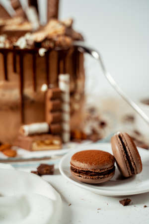 Chocolate cake decorated with various cookies and nuts on a glass plate and macaroons. Food photography. Advertising and commercial close up design