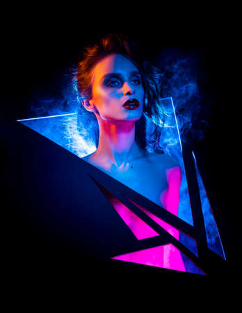 Creative conceptual portrait of a beautiful slim sexy girl with her head thrust into the triangular slots through which smoke and rays of blue and pink light emerge. Artistic, futuristic design.