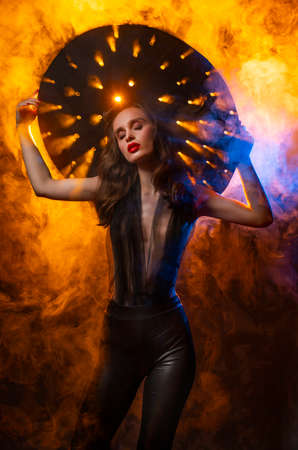 A beautiful slim sexy girl with evening make-up and red lips, wearing a large hat with holes through which rays of light shine, posing in colorful smoke. Artistic, conceptual, advertising design.