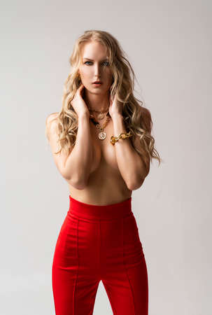 A beautiful blonde curly girl wearing a red pants and a blouse, unbuttoned on her braless big breasts, sensually poses, touching herself. Advertising, fashionable, commercial, design. Фото со стока