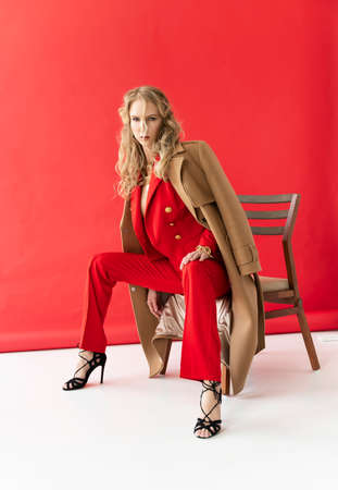 A beautiful blonde curly girl wearing a red pants and a blouse, unbuttoned on her braless big breasts, sensually poses, touching herself. Advertising, fashionable, commercial, design.