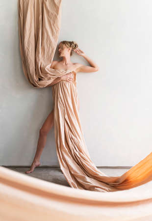 A beautiful blonde curly leggy big breasted naked girl sensually poses sitting on the floor at the wall, covering herself with a large piece of beige cloth. Copy space. Artistic design. Фото со стока