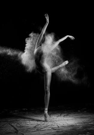 A beautiful slender ballet dancer girl wearing a bodysuit, sensually poses among the flying flour which covers her body, on a black background. Artistic, commercial, monochrome design.