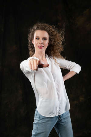 A beautiful girl, wearing jeans and a blouse, cheerfully points her finger to front, posing in the wind, which blows her long curly hair and clothes. Close up. Advertising, commercial, design. Фото со стока