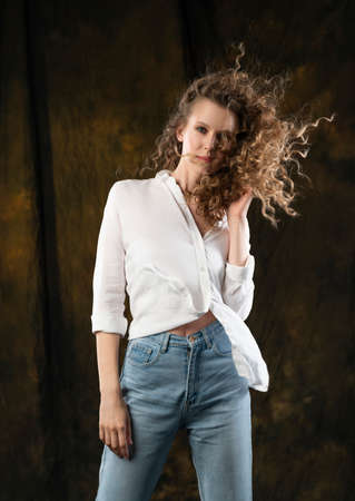 A beautiful girl, wearing jeans and a blouse, poses cheerfully in the wind, which blows her long curly hair and clothes. Advertising, commercial design.