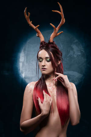 A beautiful sexy redhead topless girl, with deer horns on her head and sequins on her body, sensually posing, covering her naked breasts with her long hair. Conceptual, commercial, christmas design. Фото со стока