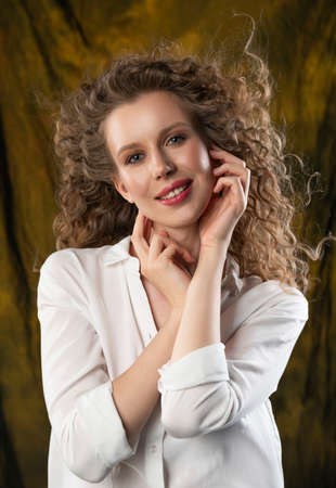 A beautiful girl, wearing jeans and a blouse, poses cheerfully in the wind, which blows her long curly hair and clothes. Close up. Advertising, commercial, design.