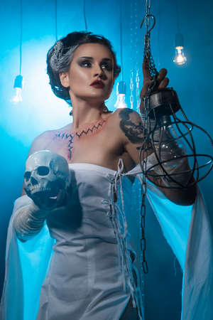 Girl wearing a Halloween costume with rich make-up and an imitation of an autopsy seam on her chest is emotionally posing in decorations holding a skull in her hands. Holiday, artistic design. Фото со стока