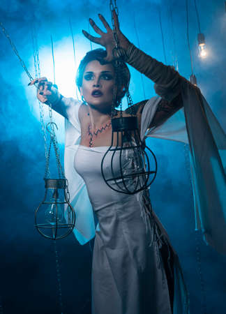 A beautiful girl wearing a Halloween carnival costume with rich make-up and an imitation of an autopsy seam on her chest is emotionally posing in decorations in blue smoke. Holiday, commercial design.