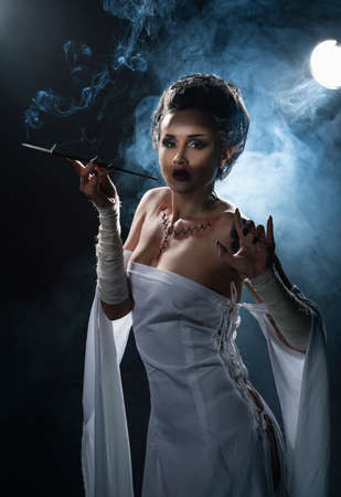 Beautiful girl wearing a Halloween costume with rich make-up and an imitation of an autopsy seam on her chest is emotionally posing holding a cigarette holder in the smoke. Vintage, cosplay design. Фото со стока