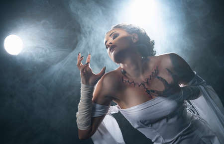 Beautiful girl wearing a Halloween costume with rich make-up and an imitation of an autopsy seam on her chest is emotionally posing in the smoke. Vintage, cosplay, artistic design.