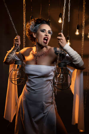 A beautiful girl wearing a Halloween carnival costume with rich make-up and an imitation of an autopsy seam on her chest is emotionally posing in decorations. Artistic, holiday, commercial design.