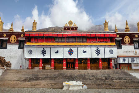 View of the front yard of the Sera Monastery in Lhasa, Tibet, with white walls against a blue sky covered by white clouds.