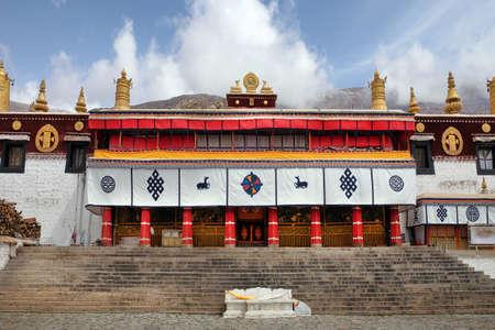 Vue sur la cour avant du monastère de Sera à Lhassa, au Tibet, avec des murs blancs contre un ciel bleu couvert de nuages blancs.