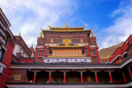 Vista frontale di un muro all'interno del Monastero di Tashilhunpo, a Shigatse, contro un cielo azzurro ricoperto da pareti bianche.