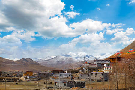View of traditional Tibetan village against the Himalayan Mountains, against a blue sky covered by white clouds.