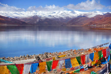 Tibetan praying flags in front of the Yamdrok Lake, reflecting the brown colors of Mt. Naiqinkangsang against a blue clear sky.